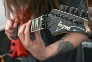 Hand on an Ibanez guitar fret board