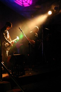 Man playing guitar on stage, there is a spotlight from stage right shining on him