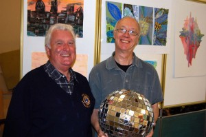 Alan Gilbert from Knaresborough Lions Club and Mark stood in front of some artwork, Mark is holding the orb disco ball
