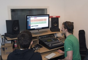 Two young men sat at a computer in a recording studio booth