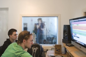 Two young men sat at a computer in a recording studio booth in the background is a man singing into a microphone